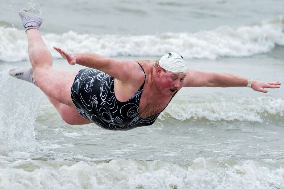 With temperatures around 8 degrees Celsius (46 degrees Fahrenheit), a man plays in the surf, with some thousands celebrating the New Year by jumping into the North Sea during the traditional New Year's Dive in Ostend, Belgium, Saturday Jan. 5, 2013. Photo: Geert Vanden Wijngaert, Associated Press / AP