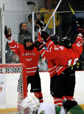 Fairfield Prep's #22 Dean Lockery, left, celebrates with teammates after he scored a goal against Notre Dame of West Haven, during boys hockey action in West Haven, Conn. on Saturday January 5, 2013. Photo: Christian Abraham / Connecticut Post