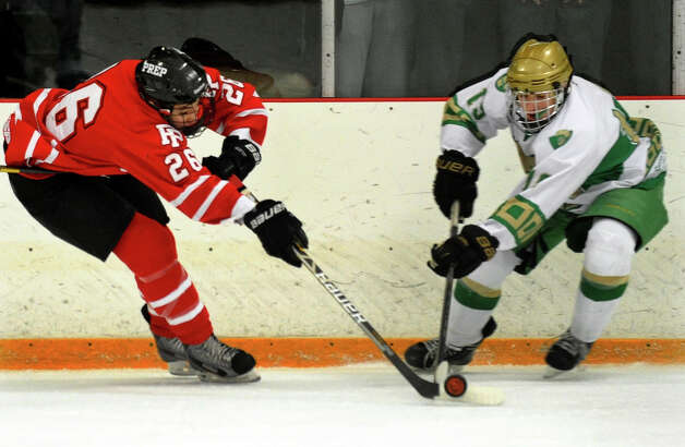 Fairfield Prep's #26 Matt McKinney, left, intercepts the puck with Notre Dame of West Haven's #19 Matthew Dostie, during boys hockey action in West Haven, Conn. on Saturday January 5, 2013. Photo: Christian Abraham / Connecticut Post