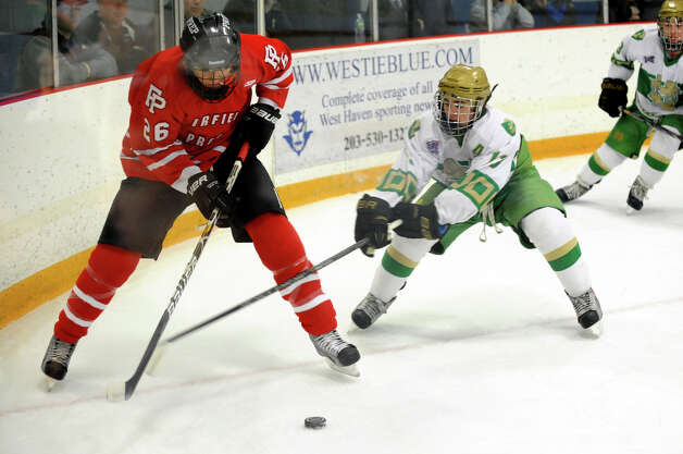 Fairfield Prep's #26 Matt McKinney, left, works to control the puck as Notre Dame of West Haven's #13 Cameron Hotchkiss tries to intercept, during boys hockey action in West Haven, Conn. on Saturday January 5, 2013. Photo: Christian Abraham / Connecticut Post