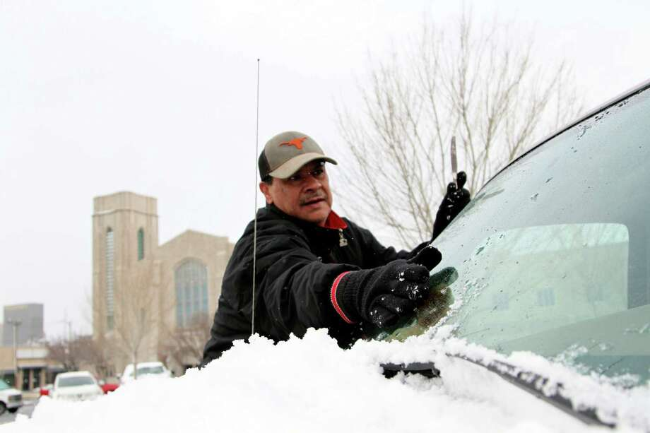 Leo Torres uses a table knife to scrape the ice off his windshield Friday, Jan 4, 2013 in El Paso. Texas. A winter storm dumped four inches of snow in the El Paso area, about half of one year's total snowfall, causing schools, businesses and government institutions to close. Photo: Juan Carlos Llorca, Associated Press / AP