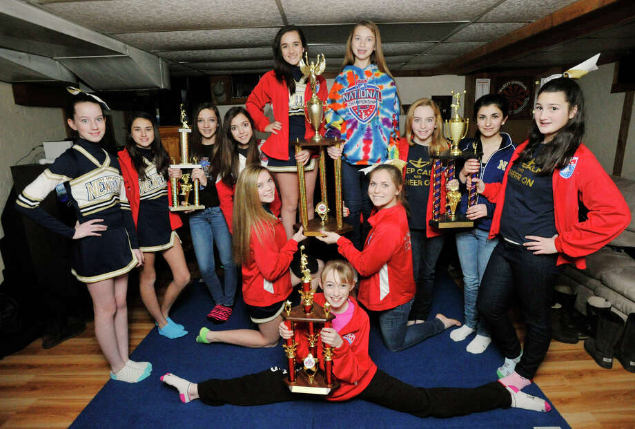 Members of the Newtown Nighthawks 8th grade -under 15 division- cheer team pose in their coach's basement with the American Youth Cheer National Championship trophy they recently won. Photographed on Saturday, Jan. 5, 2013. Photo: Jason Rearick / The News-Times