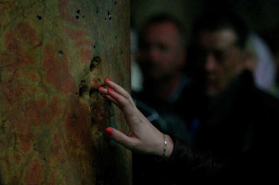 An orthodox Christian pilgrim places her fingers in a pillar as part of a traditional prayer in the Church of the Nativity, traditionally believed by Christians to be the birthplace of Jesus Christ, ahead of the Orthodox Christmas in the West Bank town of Bethlehem, Saturday, Jan. 5, 2013. Photo: Nasser Shiyoukhi, Associated Press / AP