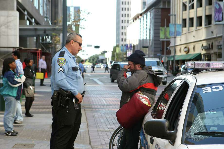 Houston Police Department's Homeless Outreach Team Mental Health Unit officer Jaime Giraldo, speaks with a homeless man about to be transported to a local hospital. Giraldo drives the HOT Mercedes Benz van, painted in classic black-and-white police colors and equipped with a powerful wheelchair lift in the rear. HPD officers assigned to HOT, or the Homeless Outreach Team, will use the roomy vehicle as a mobile office, as well as a safe transport for homeless people. The van is the latest piece of vital police equipment procured by the Houston Police Foundation, a non-profit agency. Photo: James Nielsen, Chronicle / © Houston Chronicle 2012