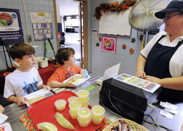 North Street School first-grade students Riccardo DeCorato, 6, left, and Brian Duffy, 5, buy pizza lunches with fruit cups from cafeteria worker Vickie Timm at the school in Greenwich, Friday, Sept. 28, 2012. Photo: Bob Luckey / Greenwich Time