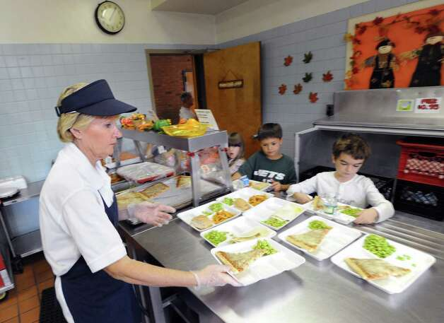 North Street School cafeteria worker Paula Thompson, left, serves pizza lunches with edamame beans to students at the school in Greenwich, Friday, Sept. 28, 2012. Photo: Bob Luckey / Greenwich Time