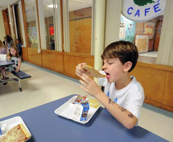 North Street School first-grade student Riccardo DeCorato, 6, eats pizza in the school cafeteria in Greenwich, Friday, Sept. 28, 2012. Photo: Bob Luckey / Greenwich Time