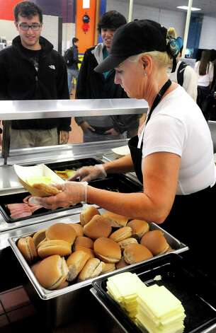 Cafeteria worker Lisa Nazzaro serves baked cheese and ham at Danbury High School Thursday, Oct. 11, 2012. Photo: Michael Duffy / The News-Times