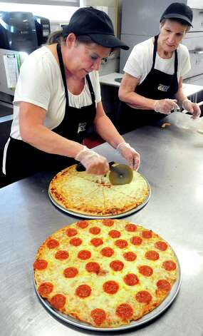 Cafeteria workers Janice Edmond, left, and Terry Molinaro make pizza for lunch at Danbury High School Thursday, Oct. 11, 2012. Photo: Michael Duffy / The News-Times