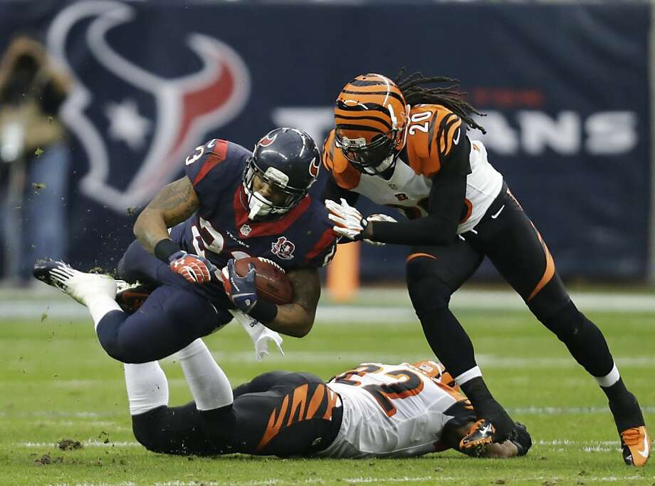 The Bengals' Reggie Nelson (right) tackles Arian Foster, who carried 32 times for 140 yards for Houston. Photo: Eric Gay, Associated Press