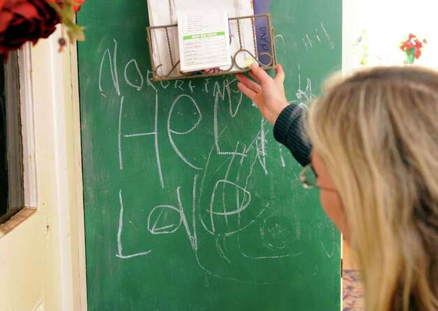 Scarlett Lewis, of Sandy Hook, looks at a note that her son Jesse wrote on the chalk board of the family home in Newtown. It reads ... Photo: Carol Kaliff / The News-Times