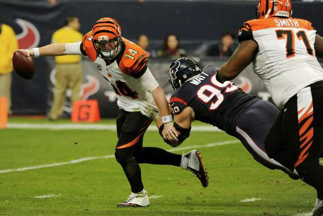 Houston Texans defensive end J.J. Watt (99) goes after Cincinnati Bengals quarterback Andy Dalton (14) during the third quarter of an NFL wild card playoff football game Saturday, Jan. 5, 2013, in Houston. (AP Photo/Dave Einsel) Photo: Dave Einsel, Associated Press / AP