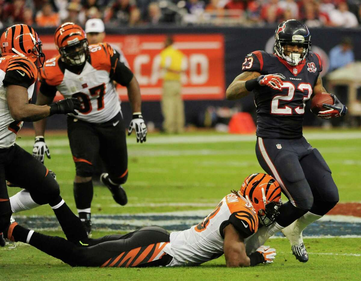 Houston Texans running back Arian Foster (23) is tackled by Cincinnati Bengals defensive end Michael Johnson (93) during the third quarter of an NFL wild card playoff football game Saturday, Jan. 5, 2013, in Houston. (AP Photo/Dave Einsel)