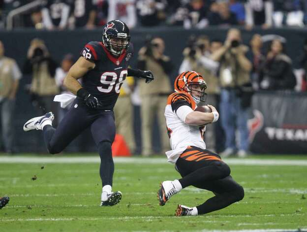 Cincinnati Bengals quarterback Andy Dalton (14) slides to end the play as Houston Texans outside linebacker Connor Barwin (98) pursues during the second quarter of an NFL wild card playoff football game Saturday, Jan. 5, 2013, in Houston. (AP Photo/Patric Schneider) Photo: Patric Schneider, Associated Press / AP