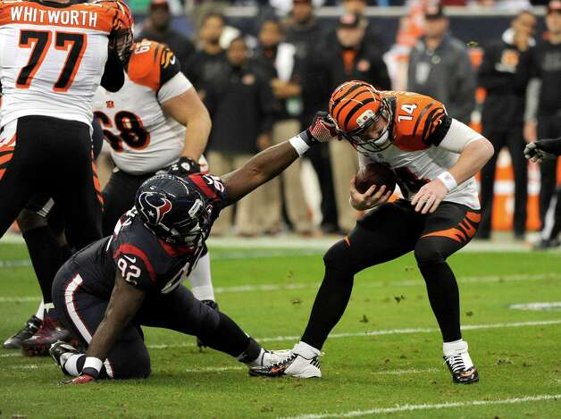 Houston Texans' Earl Mitchell (92) grabs Cincinnati Bengals quarterback Andy Dalton (14) during the first quarter of an NFL wild card playoff football game Saturday, Jan. 5, 2013, in Houston. (AP Photo/Dave Einsel) Photo: Dave Einsel, Associated Press / AP