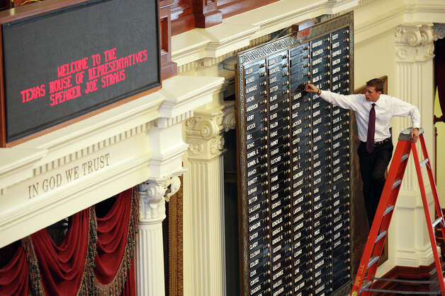 Texas House of Representatives assistant sergeant-at-arms Trevor Rice arranges names on the electronic voting board in the House Chambers at the State Capitol on Thursday in Austin. The 150-member house will have 44 newly elected members. Photo: Jerry Lara, San Antonio Express-News / © 2012 San Antonio Express-News