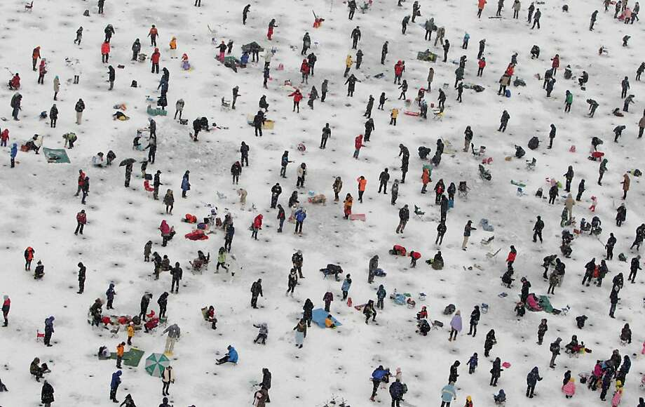 Anglers cast lines through holes into a frozen river during an ice fishing competition at the Hwacheon Sancheoneo Ice Festival on January 5, 2013 in Hwacheon-gun, South Korea. The annual event attracts thousands of visitors and features a mountain trout ice fishing competition in which participants compete with tradition lures or with bare hands. Photo: Chung Sung-Jun, Getty Images