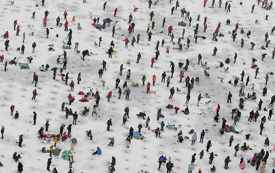 Anglers cast lines through holes into a frozen river during an ice fishing competition at the Hwache