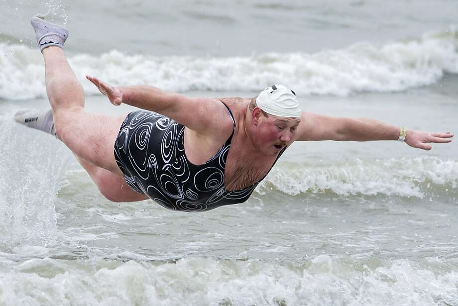 The one-piece is an excellent choice to keep one's bosoms under control: A Belgian cannonballs into the North Sea during the traditional New Year's Dive in Ostend. Photo: Geert Vanden Wijngaert, Associated Press