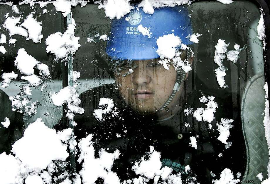 A worker looks through a snow-covered bus window while on his way to inspect electric power transmission lines after heavy snow in Huaibei, in central China's Anhui province. China Meteorological Administration says the country's average temperature has hit the lowest in 28 years this winter, as snow and ice throughout China have closed highways, canceled flights and stranded travelers. The figures released by the administration on Friday, Jan. 4, 2013 show the national average was -3.8 degrees Celsius (25 degrees Fahrenheit) since late November.  Photo: Associated Press