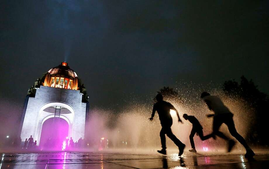 People run through a water fountain in front of the illuminated Revolution Monument in Mexico City, late Friday, Jan. 4, 2013. The once-neglected plaza with an Arc de Triumph-style monument to Mexico's 1910 revolution has been remade from a homeless encampment to a place where families visit and children run through spurts of water gushing out of the pavement. Mexico City's government is trying to transform one of the world's largest cities by beautifying public spaces, parks and monuments. Photo: Julio Cortez, Associated Press