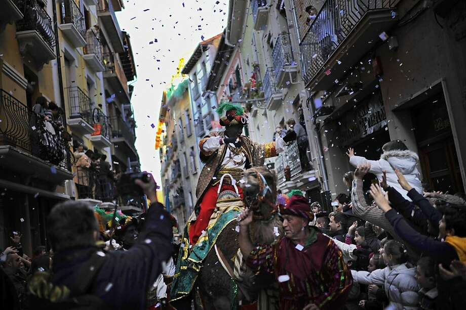 People enjoy the Cabalgata Los Reyes Magos (Cavalcade of the three kings) the day before  Epiphany, in Pamplona, northern Spain on Saturday, Jan. 5, 2013. It is a parade symbolizing the coming of the Magi to Bethlehem following the birth of Jesus. In Spain and many Latin American countries Epiphany is the day when gifts are exchanged. Photo: Alvaro Barrientos, Associated Press