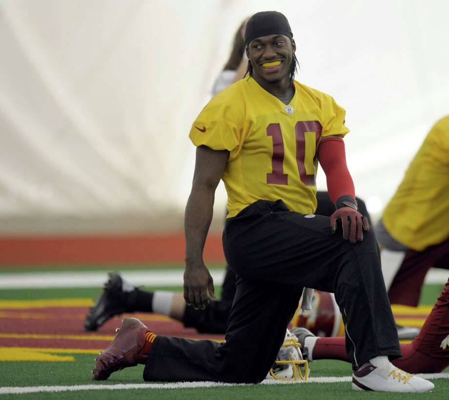 Washington Redskins quarterback Robert Griffin III stretches during a team workout at Redskins Park in Ashburn, Va., Wednesday, Jan. 2, 2013. The Redskins are working out before Sunday's wild card game against the Seattle Seahawks. (AP Photo/Susan Walsh) Photo: Susan Walsh
