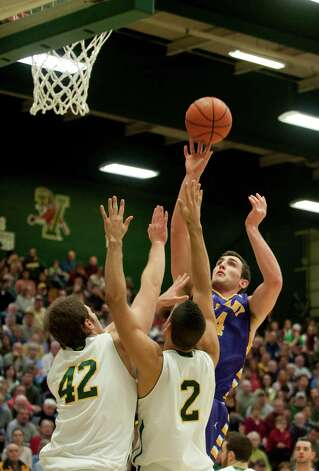 Albany's John Puk (44) leaps over Vermont's Ben Crenca (42) and Luke Apfeld (2) to take a shot during the men's basketball game between the Albany Great Danes and the Vermont Catamounts at Patrick Gymnasium on Saturday afternoon January 5, 2013 in Burlington, Vermont. (BRIAN JENKINS, for the Free Press) Photo: Brian Jenkins
