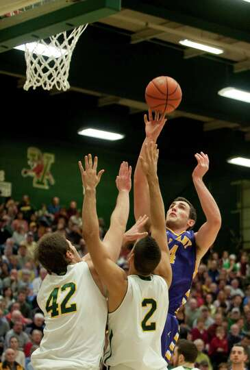 Albany's John Puk (44) leaps over Vermont's Ben Crenca (42) and Luke Apfeld (2) to take a shot durin