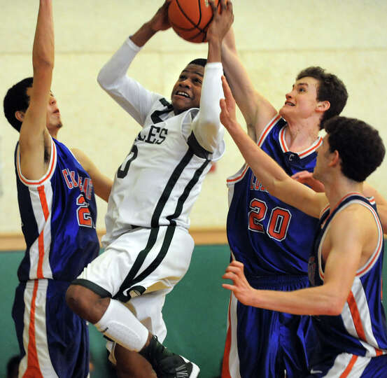 Green Tech's Najee Ward (0), center, shoots for the hoop as Collegiate's Cole Chang (21), left, Henr
