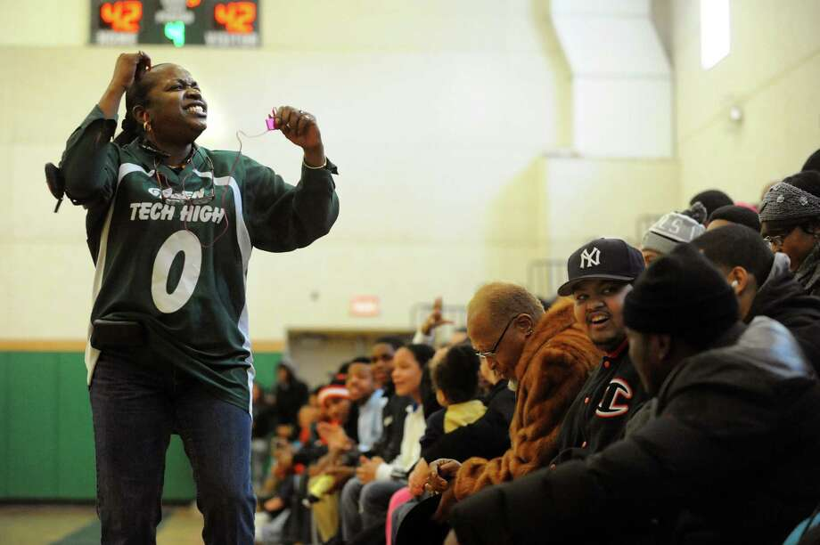 Global Studies teacher Teresa Haig-Nicol, left, leads a cheer when Green Tech and Collegiate are at a 42-42 tie during their basketball game on Saturday, Jan. 5, 2013, at Green Tech High Charter School in Albany, N.Y. Green Tech wins 59-49. (Cindy Schultz / Times Union) Photo: Cindy Schultz / 00020645A