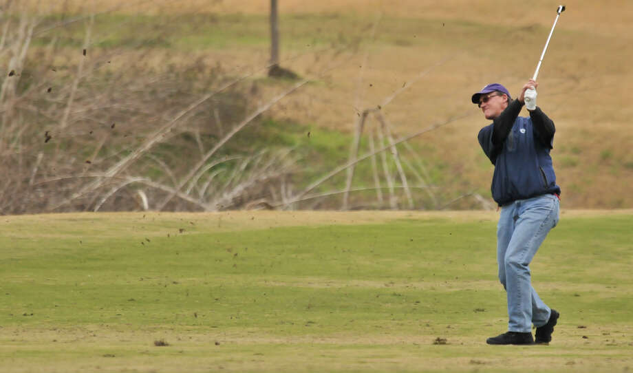 The dirt flies as Bobby Baugh hits an approach shot toward the 17th hole during the Greater San Antonio Tournament of Champions at Brackenridge Golf Course Saturday. Photo: Robin Jerstad, Express-News