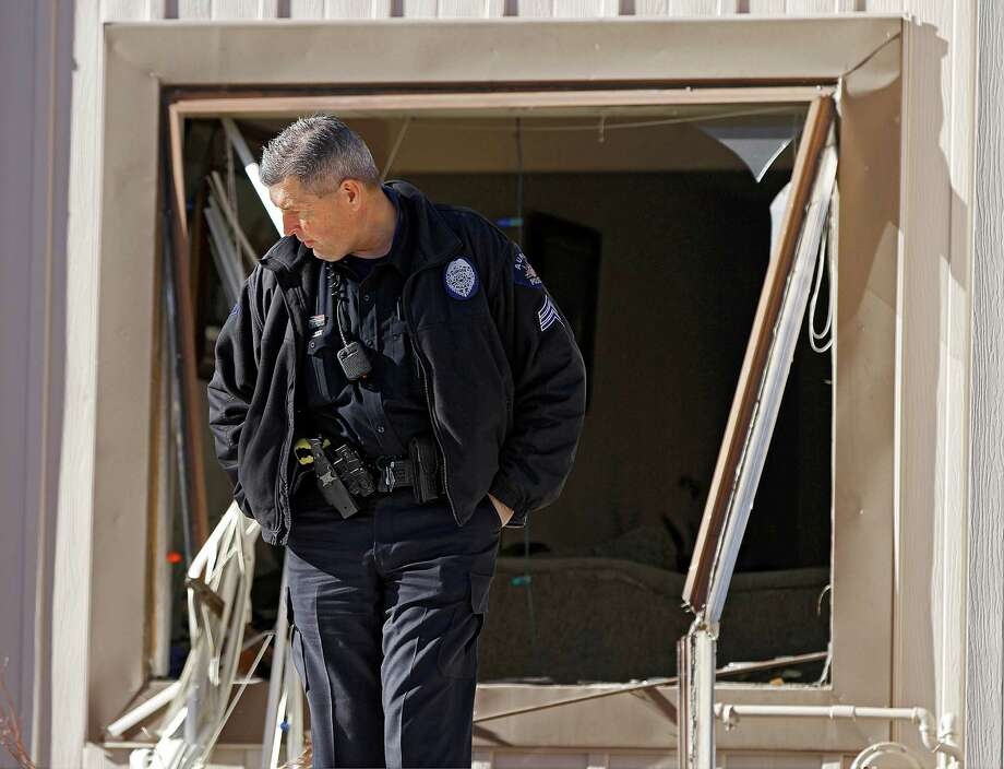 A police officer stands watch Saturday at a townhome in Aurora, Colo., where four people were killed in a standoff with police. In July, 12 people died and 58 were wounded in a shooting at an Aurora movie theater. Photo: Marc Piscotty, Stringer / 2013 Getty Images