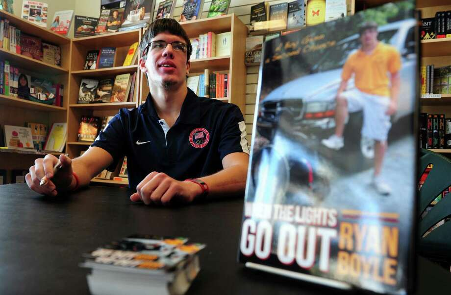 "Ryan Boyle, a former Monroe resident and Traumatic Brain Injury survivor, signs copies of his autobiography ""When the Lights Go Out"" Saturday, Jan. 5, 2013  at Linda's Story Time in Monroe, Conn. Photo: Autumn Driscoll / Connecticut Post"