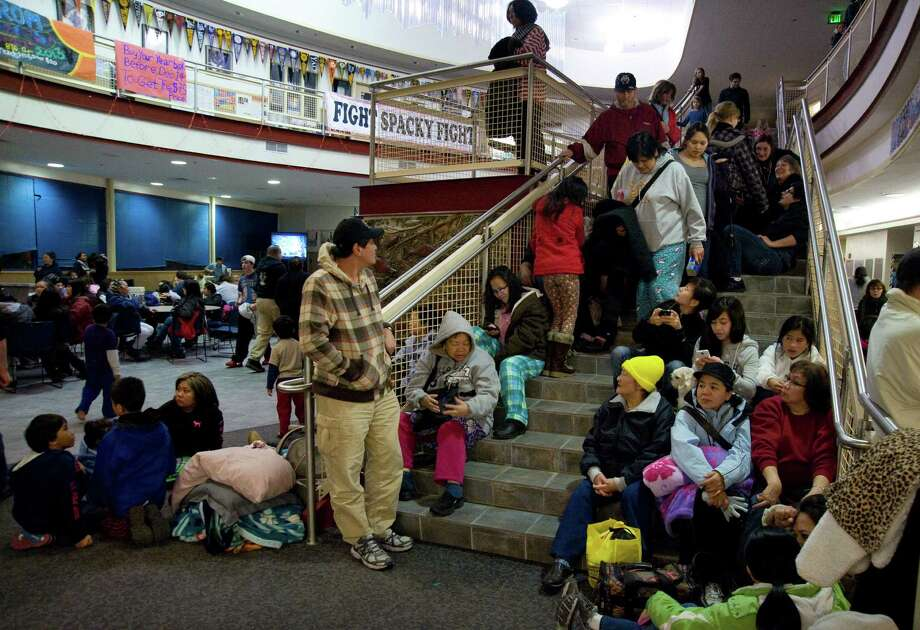 People gather at Sitka High School early Saturday, Jan. 5, 2013, in Sitka, Alaska, following a magnitude 7.5 earthquake and after a subsequent tsunami warning was declared for hundreds of miles of Alaskan and Canadian coastline. The alert was canceled when no damaging waves were generated. (AP Photo/Daily Sitka Sentinel, James Poulson) Photo: James Poulson