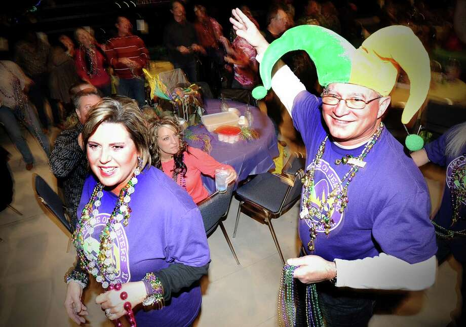 Krewes parade through the crowd throwing beads during the presentation of Krewes at the Beans and Jeans party at the Carl A. Parker Center on the Lamar State College Port Arthur campus on Saturday, January 5, 2013.  The Beans and Jeans party is a brand new Mardi Gras Southeast Texas event that is hosted by  the Krewe of Krewes.  The event featured live music by Champagne Room. Photo taken: Randy Edwards/The Enterprise Photo: Randy Edwards