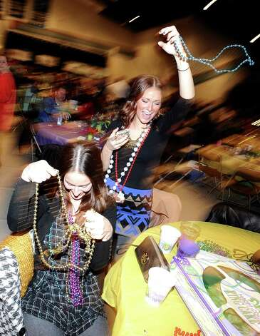 Hillary and Mallory Petry snag up beads during the presentation of Krewes  at the Beans and Jeans party at the Carl A. Parker Center on the Lamar State College Port Arthur campus on Saturday, January 5, 2013.  The Beans and Jeans party is a brand new Mardi Gras Southeast Texas event that is hosted by  the Krewe of Krewes.  The event featured live music by Champagne Room. Photo taken: Randy Edwards/The Enterprise Photo: Randy Edwards