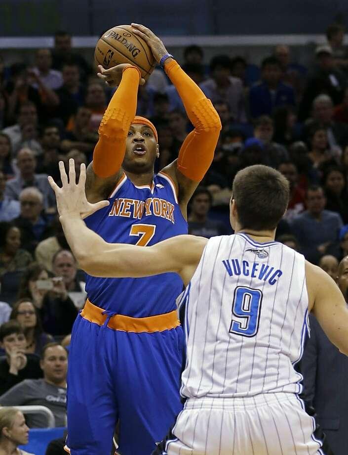 New York's Carmelo Anthony, who had 40 points, takes aim over Orlando's Nikola Vucevic. Photo: John Raoux, Associated Press