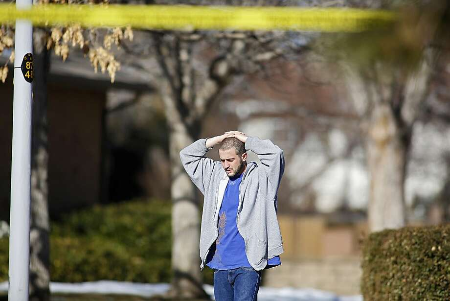 A neighbor takes in the scene at a town home where four people were killed Saturday morning including the gunman who held police at bay for several hours at the complex January 5, 2013 in Aurora, Colorado. Aurora SWAT team members shot a gunman after he went to a second-floor window and fired at police. The gunman also allegedly fatally shot two men and a woman that he had taken hostage. One woman managed to escape from an upstairs back window, ran from the home and called police just before 3 a.m., said Cassidee Carlson, Aurora police spokeswoman. Photo: Marc Piscotty, Getty Images