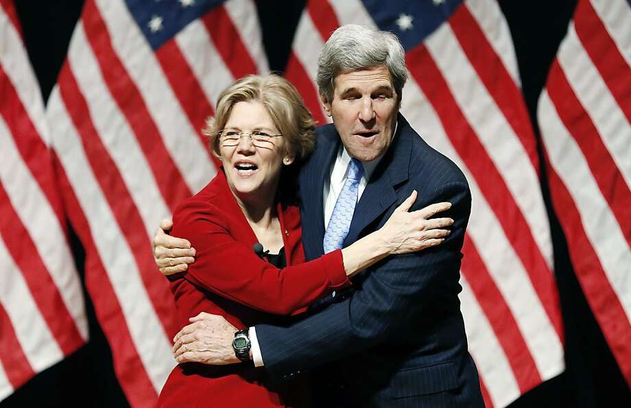 Sen. Elizabeth Warren, D-Mass., left, hugs Sen. John Kerry, D-Mass., right, before a re-enactment of her swearing-in ceremony at Roxbury Community College in Boston, Saturday, Jan. 5, 2013. Photo: Michael Dwyer, Associated Press