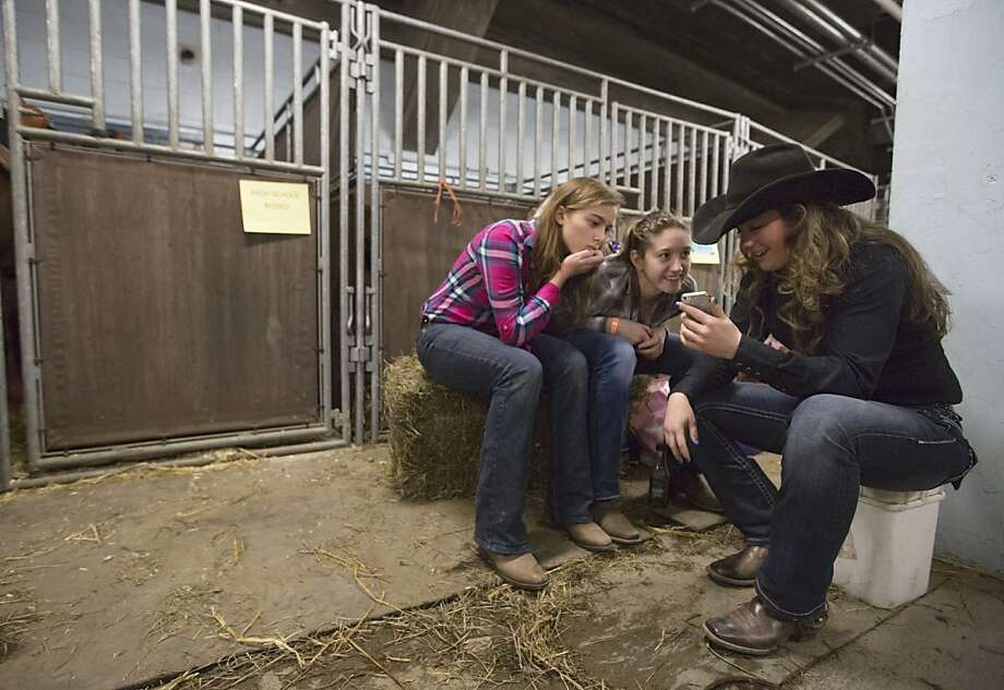 From left, Autumn Scolari, Desiray Trick and Kayla Harris pass some time on the Internet before the High School Rodeo competition at the Pennsylvania Farm Show, Saturday, Jan. 5, 2013 in Harrisburg, Pa. Photo: Joe Hermitt, Associated Press