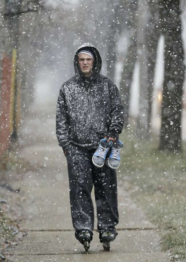 A man holds his shoes as he skates on the sidewalk as snow falls in Chicago, Saturday, Jan. 5, 2013. Weather forecasters say dry weather will dominate early next week before a storm moves into the Midwest, likely bringing Chicago more rain than snow. Photo: Nam Y. Huh, Associated Press