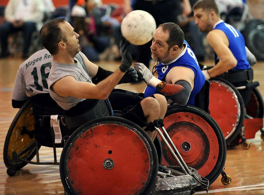 Magee's Eric Anderson, left, battles for control of the ball with Bandits' Don Bergman, right, during a match between the Brooks Bandits Blue quad rugby team, from Jacksonville, Fla., and the Magee Eagles, from Philadelphia, Saturday, Jan. 5, 2013, in Jacksonville, Fla. The Brooks Rehabilitation Adaptive Sports and Recreation and the East Arlington Rotary Club held the Sixth Annual Southern Slam Quad Rugby Tournament in the Jacksonville Ice and Sportsplex Photo: Bob Mack, Associated Press
