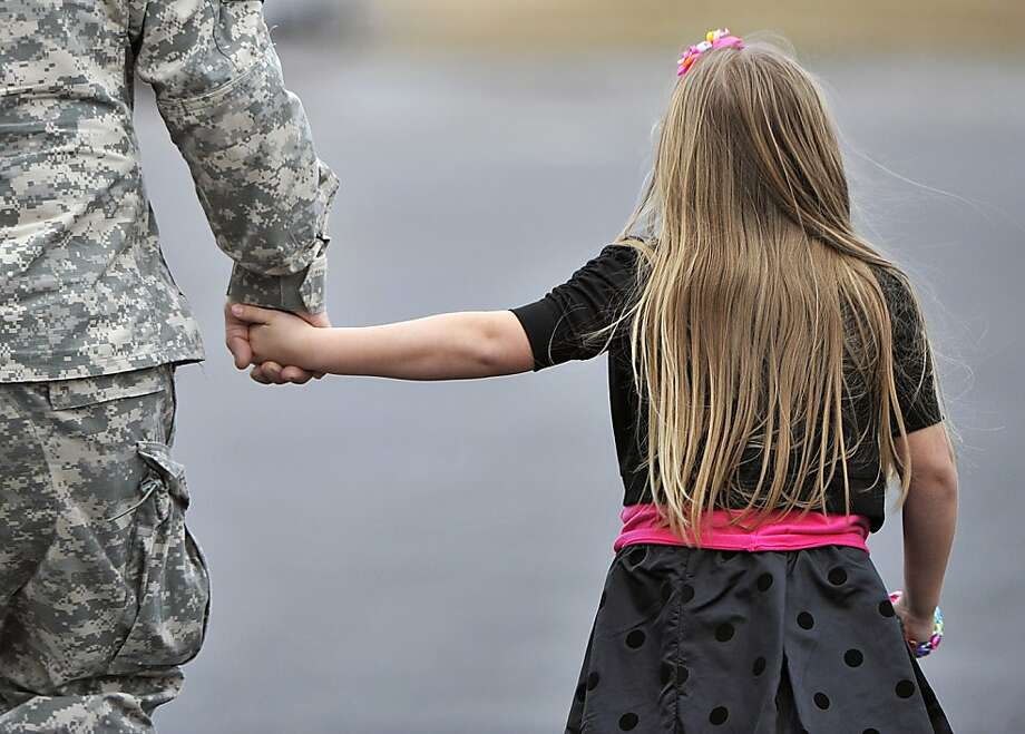 Sgt. Dennis Stough and his daughter Savannah hold hands at a deployment ceremony Saturday, Jan. 5, 2013,  in Huntsville, Ala., for the Alabama Army National Guard 128th Military Police Company, leaving for Guantanamo Bay, Cuba. Photo: Bob Gathany, Associated Press