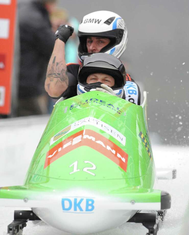 Germany's  Thomas Florschuetz  front , and Kevin Kuske  celebrate in the finish area  at the 2-men Bobsled World Cup  in Altenberg, Germany, Saturday Jan. 5, 2013. Thomas Florschuetz, Germany 2  and Francesco Friedrich Germany 1  shared victory and led a German sweep of the top three positions at a World Cup two-man bobsled event on Saturday. Olympic silver medallist Florschuetz and brakeman Kevin Kuske were inseparable from Germans  Francesco  Friedrich and Jannis Baecker after two runs. It was junior world champion Friedrich's first ever World Cup victory (AP Photo/dapd/ Matthias Rietschel) Photo: Matthias Rietschel