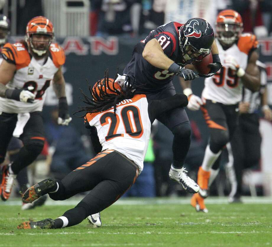 An integral part of the passing attack, Owen Daniels (81) and the rest of the Texans' tight ends found themselves having to go through, over or around Bengals defenders like Reggie Nelson (20) in Saturday's playoff win. Photo: Karen Warren, Staff / © 2012 Houston Chronicle
