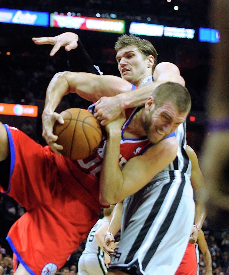 Tiago Splitter (top) of the Spurs, and Spencer Hawes of the Philadelphia 76ers battle for a rebound in the AT&T Center on Saturday, Jan. 5, 2013. Photo: Billy Calzada, San Antonio Express-News / SAN ANTONIO EXPRESS-NEWS