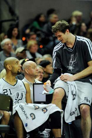 Tim Duncan (left) and Tiago Splitter of the Spurs speak during a timeout of their game against Philadelphia in the AT&T Center on Saturday, Jan. 5, 2013. Photo: Billy Calzada, San Antonio Express-News / SAN ANTONIO EXPRESS-NEWS