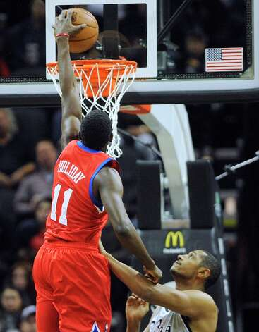 Jrue Holiday (11) of the Philadelphia 76ers dunks over Boris Diaw of the Spurs during first-half action in the AT&T Center on Saturday, Jan. 5, 2013. Photo: Billy Calzada, San Antonio Express-News / SAN ANTONIO EXPRESS-NEWS