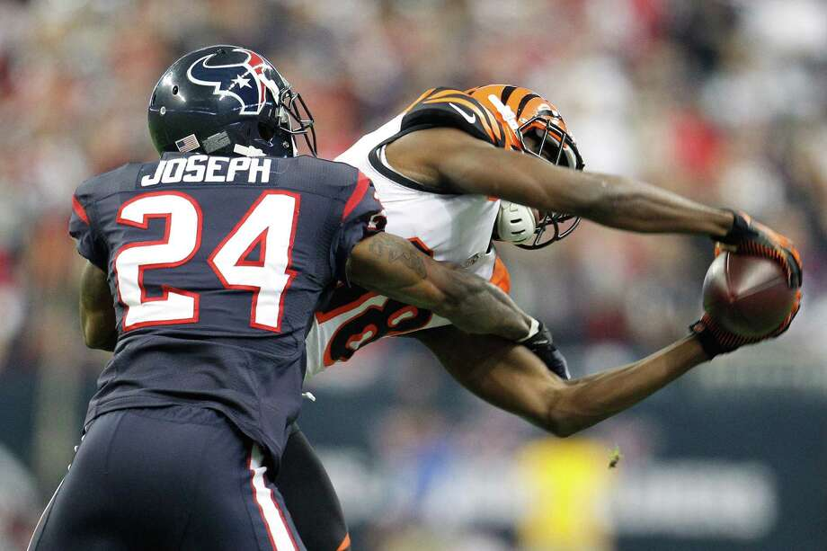 Texans cornerback Johnathan Joseph (24) tackles Bengals Cincinnati Bengals wide receiver A.J. Green (18) as he catches the pass during the third quarter. Photo: Karen Warren, Houston Chronicle / © 2012 Houston Chronicle